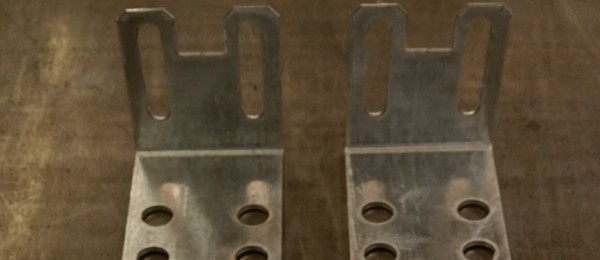 A pair of punched angle brackets made from galvanised steel