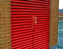 A louvred aluminium door providing access and natural ventilation to a plant room in Bolton