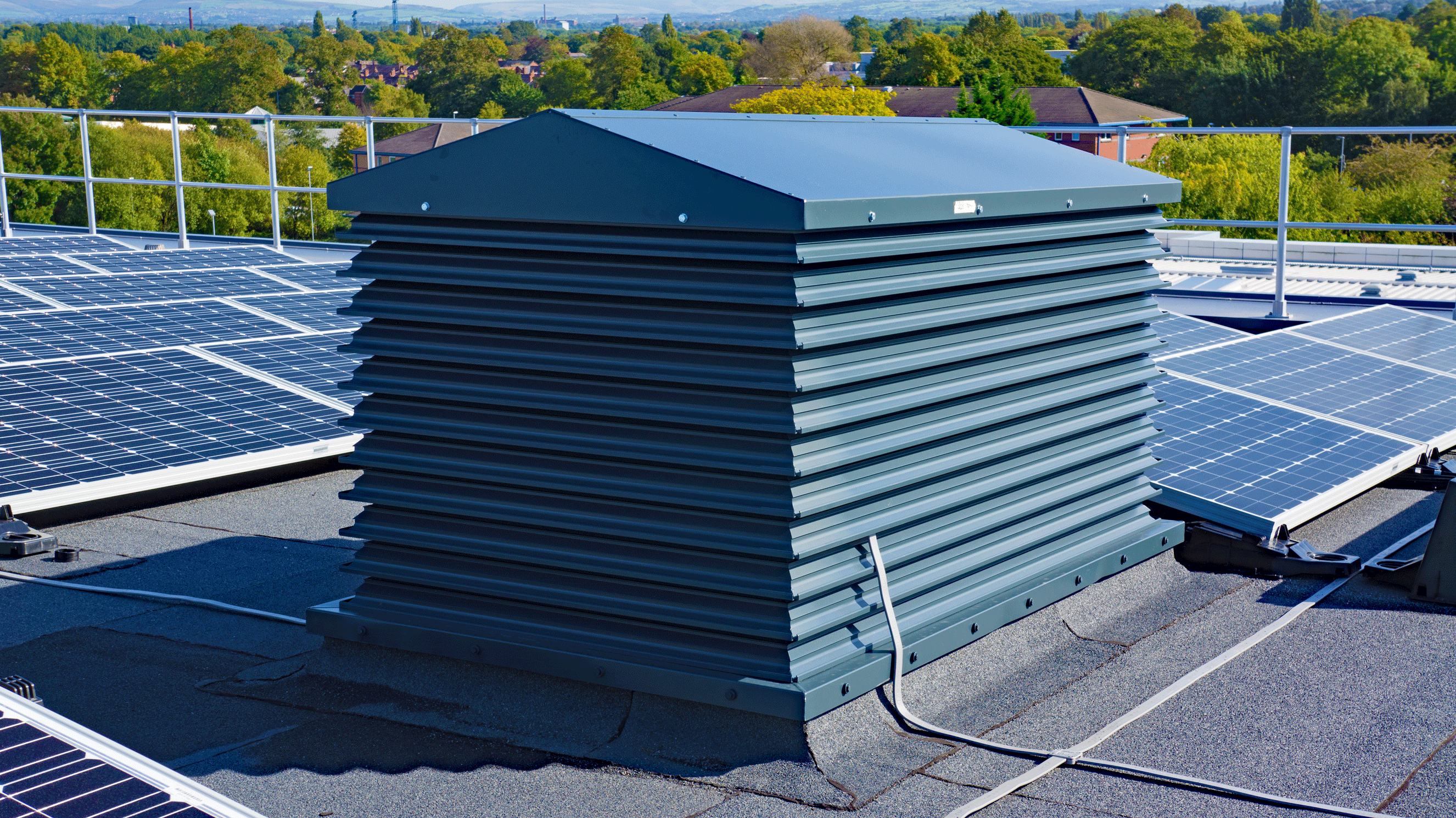 Our A Series grey painted natural ventilation louvred turret in-situ on a roof in Manchester
