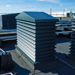 A group of A Series grey painted natural ventilation louvred turrets in-situ on a roof in Manchester