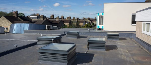 A group of natural ventilation louvre rooflight turrets painted grey and installed into a school in London