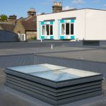 An external view of a natural ventilation louvre rooflight turret painted grey and installed into a school in London