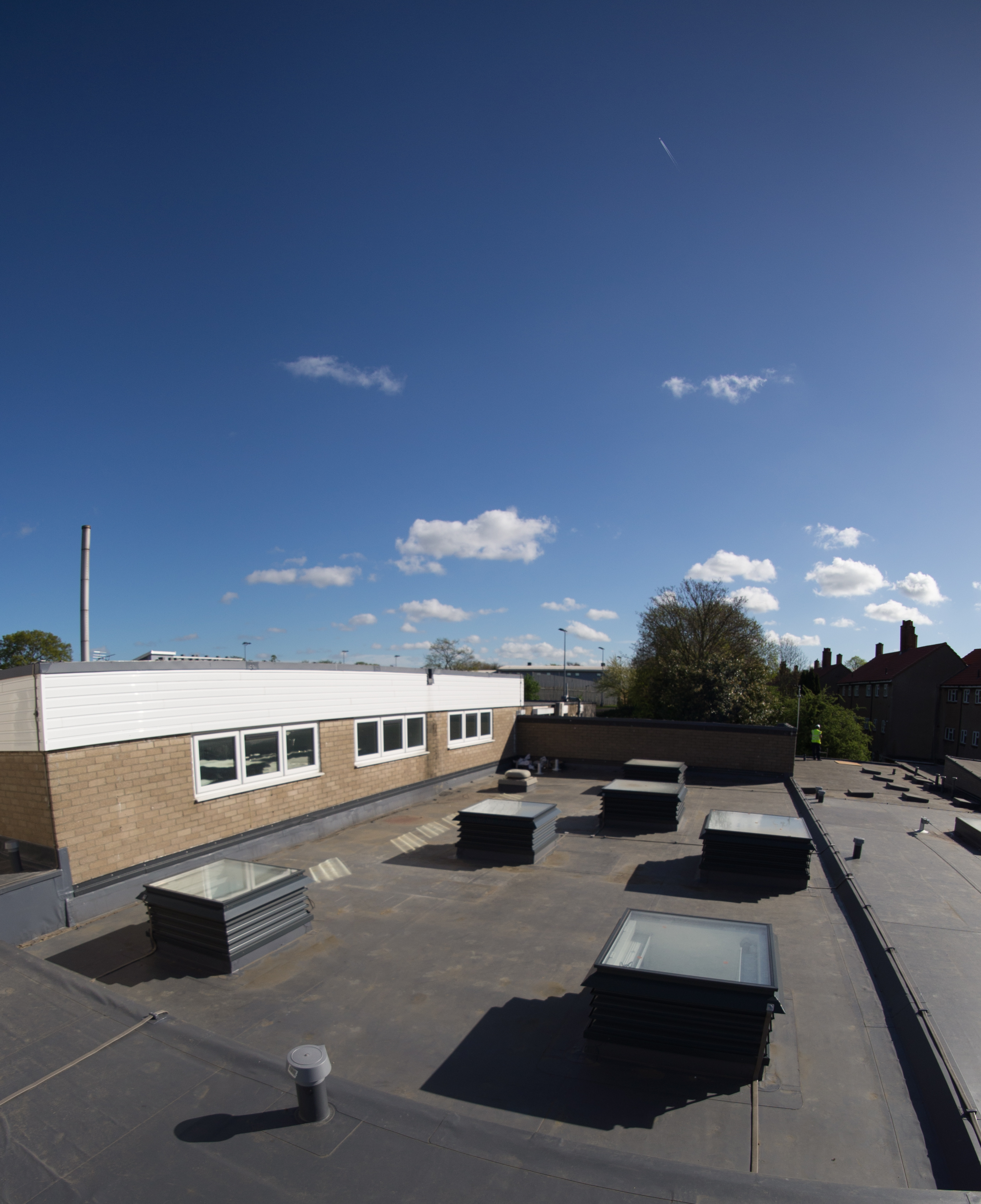 A group of a natural ventilation louvre rooflight turrets painted grey and installed into a school in London