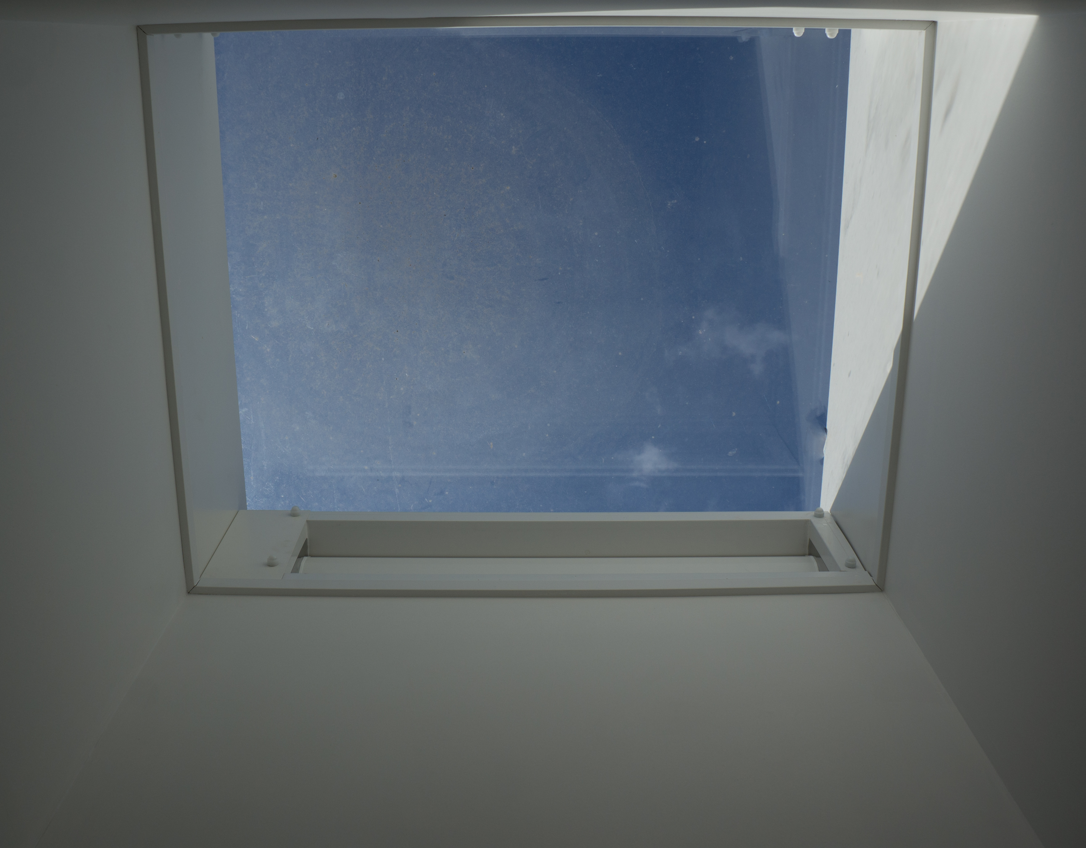 An internal view of a natural ventilation louvre rooflight turret painted white and installed into a school in London