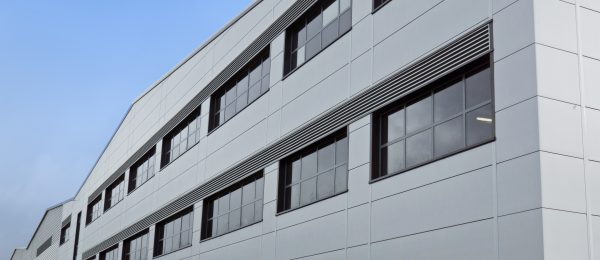 PPC finish aluminium continuous fixed louvres by McKenzie Martin installed into a grey building in Pilsworth